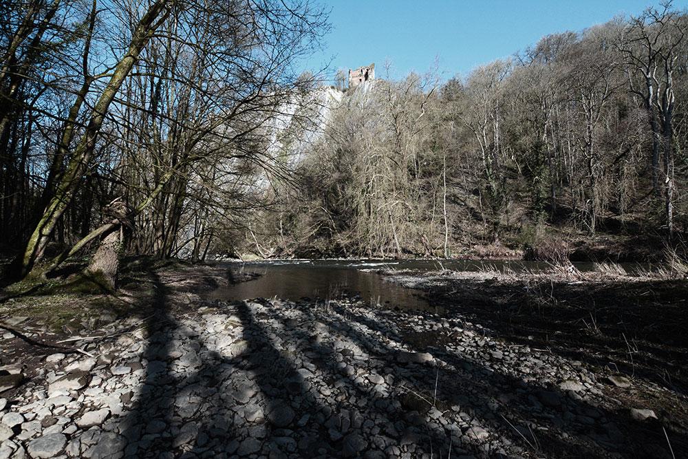 Une rivière en fôret, surplombé par une ruine sur une falaise